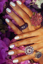 Bright colorfull shot of african tanned hands with manicure among pink flowers wearing jewellery among flowers Royalty Free Stock Photo