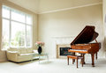 Bright daylight living room with grand piano fireplace sofa and large window coming through Royalty Free Stock Images
