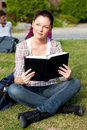 Bright female student reading a book on the grass Stock Photography
