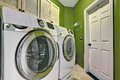 Bright green laundry room interior small birhgt with white modern appliances Royalty Free Stock Photos