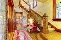 Bright hallway with colourful rug, nice red sofa, wooden stairca