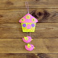 Bright house with birds ornament isolated on wooden background. Beautiful house with birds sewn from pink, purple and yellow felt Royalty Free Stock Photo