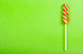 Bright juicy colored lollipop on a green paper background. Lollipop in the form of a color spiral. Fruit candy. Royalty Free Stock Photo