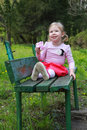The bright little girl sits on the bank of a park, smiles Royalty Free Stock Photo