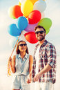 Bright love cheerful young couple holding hands and smiling while walking outdoors with colorful balloons Stock Photos