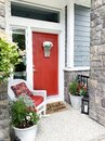 Bright orange front door and porch with a wicker chair. Colorful entrance Royalty Free Stock Photo