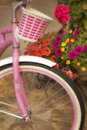 Bright pink bicycle and basket with colorful flowers this white matching is parked next to a flower arrangment on a stone patio Royalty Free Stock Images