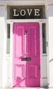 Bright pink door on a white wall with Love on top Royalty Free Stock Photo