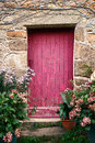 Bright pink paint wood door on old stone house with crooked archway an framed with flowers in a quaint village in france Stock Images