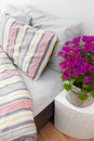 Bright purple flowers decorating a bedroom modern with striped bed linen Stock Photos