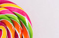 Bright rainbow round lollipop. On pink background.Copy space Royalty Free Stock Photo