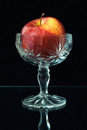 Bright red apple in a crystal vase isolated black background Royalty Free Stock Photos