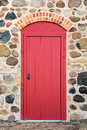 Bright Red Arched Door in a Stone Wall Royalty Free Stock Photo