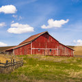 Bright red barn on clear day a under a blue sky near palouse washington Stock Photo