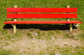 Bright red bench on a green meadow with pebbly foreground Royalty Free Stock Photos