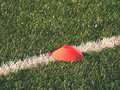 Bright red plastic cone on painted white line of soccer field. Plastic football green turf playground Royalty Free Stock Photo