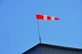A bright red windsock atop a building in the rais of the sun Stock Photography