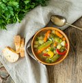 Bright spring vegetable dietary vegetarian soup. Top view, brown rustic wood background, linen napkin. Royalty Free Stock Photo
