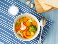 Bright spring vegetable soup with cauliflower, broccoli, pepper, carrot, green peas. Top view, blue wooden background. Royalty Free Stock Photo