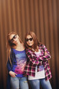 Bright stylish lifestyle urban portrait of two pretty best friends girls posing Royalty Free Stock Photo