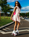 Bright summer portrait of an asian girl in a summer bright outfit and sunglasses with a pink backpack on roller skates Royalty Free Stock Photo