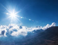 Bright sun in the sky beautiful blue cloudy over high mountains stunning cloudscape natural background fresh air summer time Royalty Free Stock Images