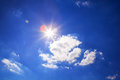 Bright sun in sky and clouds on blue Royalty Free Stock Photo