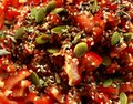 Bright tomato salad with colorful sunflower seeds as fresh healthy vegeterian food background. Royalty Free Stock Photo