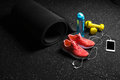 Bright training shoes, dumb-bells, stretching mat, blue bottle, and phone with headphones on a floor background. Sport