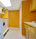 Bright yellow laundry room interior with white appliances Stock Images