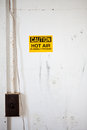 Bright yellow sticker on a dirty white wall sticker says caution hot air is usually present good for illustrating concepts like Royalty Free Stock Photos