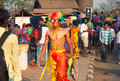 Brightly colored actor with psychedelic wig walking in crowd of people at the traditional Goa carnival