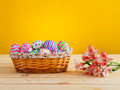 Brightly colored eggs with flowers in a wicker basket on wooden table Stock Photography