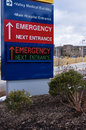 Brightly colored modern electronic hospital emergency entrance sign shown hospital buildings background vertical Royalty Free Stock Photo