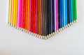 Brightly colored pencil crayons grouped together into a point ac across the top middle of horizontal image on white background Royalty Free Stock Photo