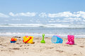 Brightly colored plastic beach toys on the beach with ocean and clouds in background Stock Photos