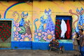 Brightly coloured mural ataco el salvador two local people walking past a painted on the walls of a street in a small town in the Stock Photos