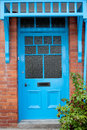 Brightly coloured traditional english house door with a plant in front of it Stock Photos