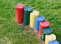 Brightly coloured tree stumps forming a barrier painted in the colours of the rainbow on green grass Royalty Free Stock Photo