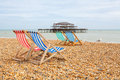 Brighton beach brighton england deckhairs on with west pier behind east sussex Royalty Free Stock Photos