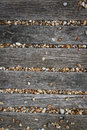 Brighton beach pebbles background covering old wooden pathway on sussex england Stock Image