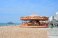 Brighton beachfront with carousel stalls and distant view of wrecked west pier for articles about british or general tourism Royalty Free Stock Photo