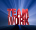Brilliant teamwork bright red on dark blue background brilliantly backlit with light rays shining through Royalty Free Stock Photo