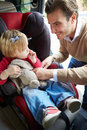 Bringen sie putting young girl in auto seat hervor Lizenzfreies Stockbild