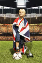 British champion young boy posing arrogantly with a flag a large trophy and a soccer ball in the center of a huge stadium Royalty Free Stock Image