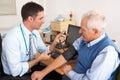 British doctor taking senior man's blood pressure Royalty Free Stock Photo