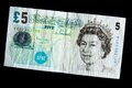 British five pound note pounds on a black background Stock Photos