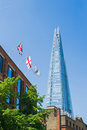 British flags on the top of a bricked building with the modern london s architecture in the background Royalty Free Stock Images