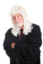 British judge skeptical style in a wig with his arms crossed and a expression isolated Stock Image