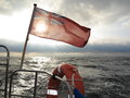 British maritime ensign flag boat and stormy sky the uk red the flown from yacht sail dark clouds baltic sea summer travel Royalty Free Stock Photo